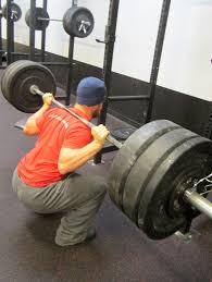 What is a good way to test if the bar is at the spine of the scapula while Squatting?